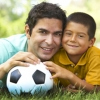 Photo of father and son with a soccer ball.