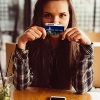 Young woman at a restaurant with her Mission Fed debit card.