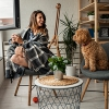 Woman enjoying her coffee in her home while talking to her dog.