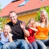 Photo of a happy family in front of their home they purchased with a Mission Fed home loan.