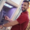 Photo of a man confidenty using an ATM with his Mission Fed credit card.