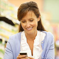 Photo of a woman checking her phone for a text message in a supermarket.