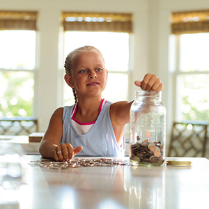 Young girl saving coins in a jar.
