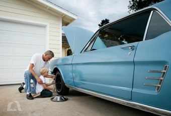 Photo of father and son working on classic car