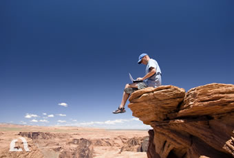 Photo of man sitting on mountain top with his laptop