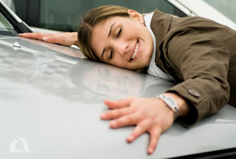 Photo of a happy woman hugging the hood of her new car.