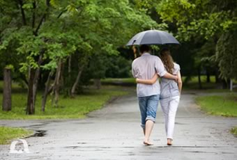 Photo of a couple walking down a park road with an umbrella.
